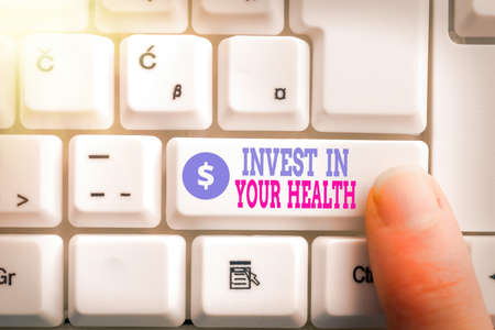 Writing note showing Invest In Your Health. Business concept for put money on maintenance or improvement of your health Pc keyboard key with pointing finger above background copy space Archivio Fotografico