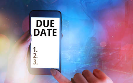 Handwriting text Due Date. Conceptual photo the day or date by which something is supposed to be done or paid Modern gadgets with white display screen under colorful bokeh background