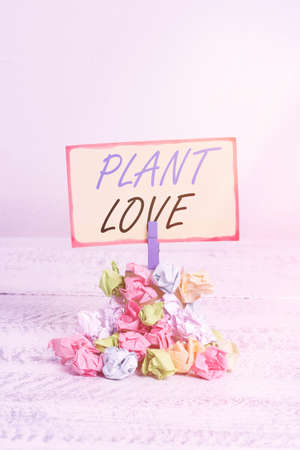 Writing note showing Plant Love. Business concept for a symbol of emotional love, care and support showed to others Reminder pile colored crumpled paper clothespin wooden space
