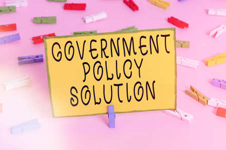 Word writing text Government Policy Solution. Business photo showcasing designed game plan created in response to emergency disaster Colored clothespin papers empty reminder pink floor background office pin Stok Fotoğraf