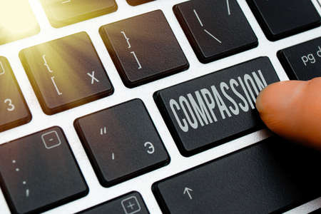 Handwriting text writing Compassion. Conceptual photo empathy and concern for the pain or misfortune of others Pc keyboard key with pointing finger above background copy space 版權商用圖片