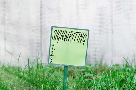 Conceptual hand writing showing Signwriting. Concept meaning any type of clear lettering intended for use on symbols Plain paper attached to stick and placed in the grassy land