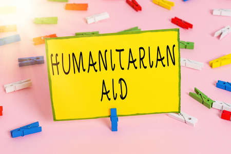 Word writing text Humanitarian Aid. Business photo showcasing immediate assistance provided after natural and manmade disaster Colored clothespin papers empty reminder pink floor background office pin