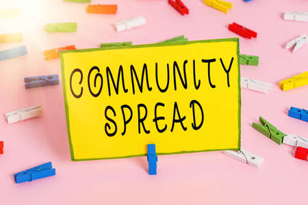 Word writing text Community Spread. Business photo showcasing dissemination of a highlycontagious disease within the local area Colored clothespin papers empty reminder pink floor background office pin