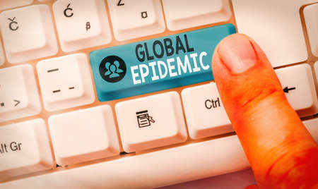 Conceptual hand writing showing Global Epidemic. Concept meaning a rapid spread of a communicable disease over a wide geographic area White pc keyboard with empty note paper above white key copy space