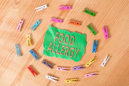 Word writing text Food Allergy. Business photo showcasing abnormal immune system response to allergen after eaten Colored clothespin papers empty reminder wooden floor background office Stock Photo