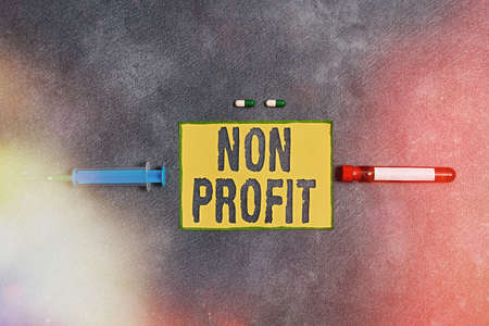 Text sign showing Non Profit. Business photo showcasing an activity not making or conducted primarily for a profit Extracted blood sample vial with medical accessories ready for examination