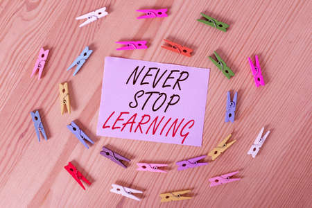 Handwriting text Never Stop Learning. Conceptual photo continuous education and techniques to be competitive Colored clothespin papers empty reminder wooden floor background office 免版税图像 - 151225754