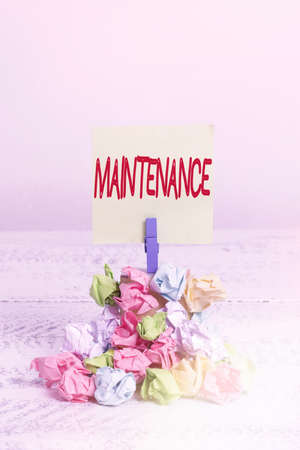 Word writing text Maintenance. Business photo showcasing method of preserving or maintaining someone or something Reminder pile colored crumpled paper clothespin reminder white wooden space Stock Photo