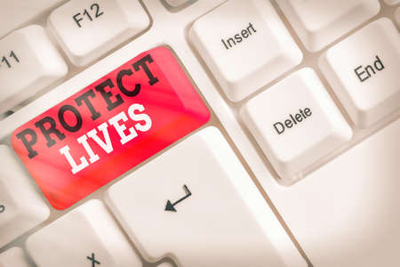 Conceptual hand writing showing Protect Lives. Concept meaning to cover or shield from exposure injury damage or destruction White pc keyboard with empty note paper above white key copy space