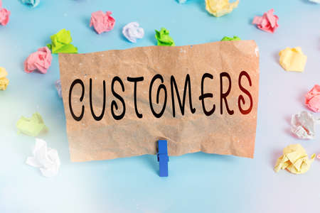 Text sign showing Customers. Business photo text individual or organization purchasing products or services Colored crumpled papers empty reminder blue floor background clothespin