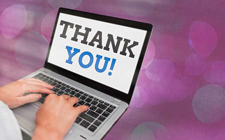 Writing note showing Thank You. Business concept for polite expression to acknowledge a gift, service or compliment Modern gadgets white screen under colorful bokeh background