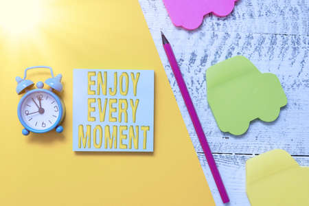 Text sign showing Enjoy Every Moment. Business photo showcasing stay positive thinking for an individualal development Notepad car sticky notes pen paper sheet alarm clock wooden background