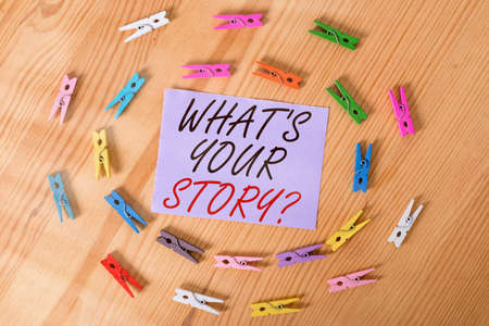 Handwriting text What S Your Story Question. Conceptual photo Share or tell us your life experiences and success Colored clothespin papers empty reminder wooden floor background office