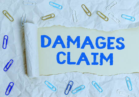 Writing note showing Damages Claim. Business concept for seeks to repair the damages or liability of the victim party Rolled ripped torn cardboard above a wooden classic table