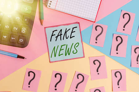 Conceptual hand writing showing Fake News. Concept meaning false information publish under the guise of being authentic news Mathematics stuff and writing equipment on pastel background