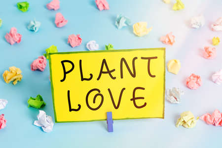 Word writing text Plant Love. Business photo showcasing a symbol of emotional love, care and support showed to others Colored crumpled papers empty reminder blue floor background clothespin