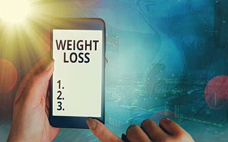 Handwriting text Weight Loss. Conceptual photo a reduction of the total body mass due to a mean loss of fluid Modern gadgets with white display screen under colorful bokeh background