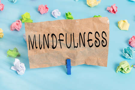 Text sign showing Mindfulness. Business photo text state of mind attained by concentrating one s is attention Colored crumpled papers empty reminder blue floor background clothespin Фото со стока