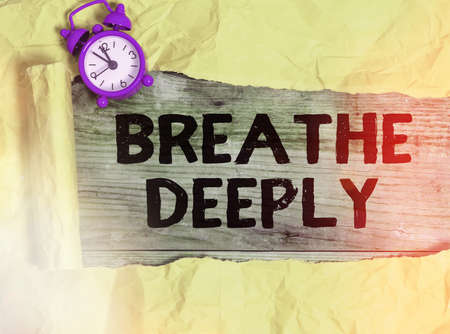 Word writing text Breathe Deeply. Business photo showcasing to take a lot of air into the lungs inhaleexhale fully Rolled ripped torn cardboard placed above a wooden classic table backdrop