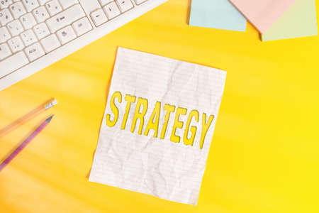 Word writing text Strategy. Business photo showcasing action plan or strategy designed to achieve an overall goal Copy space on notebook above yellow background with pc keyboard on the table