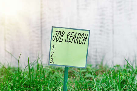 Conceptual hand writing showing Job Search. Concept meaning an act of sourcing for job openings and apply for a position Plain paper attached to stick and placed in the grassy land