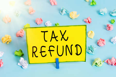 Word writing text Tax Refund. Business photo showcasing excess payment of paid taxes returned to business owners Colored crumpled papers empty reminder blue floor background clothespin 免版税图像