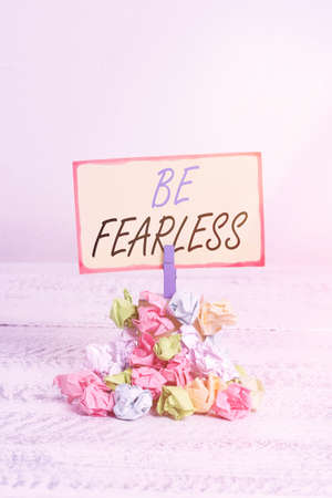Writing note showing Be Fearless. Business concept for act of striving to lead an extraordinary life and make a difference Reminder pile colored crumpled paper clothespin wooden space