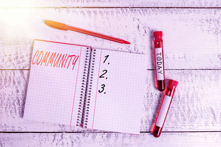 Conceptual hand writing showing Community. Concept meaning group of showing with a common characteristics living together Blood sample vial medical accessories ready for examination