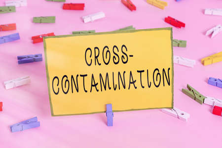Word writing text Cross Contamination. Business photo showcasing Unintentional transmission of bacteria from one substance to another Colored clothespin papers empty reminder pink floor background office pin