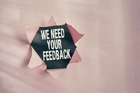 Word writing text We Need Your Feedback. Business photo showcasing Give us your ideas and suggestions on what to improve Rolled ripped torn cardboard placed above a wooden classic table backdrop Foto de archivo