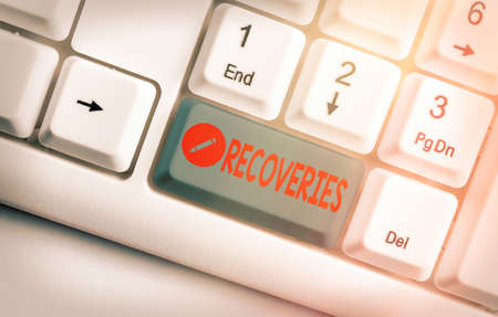 Text sign showing Recoveries. Business photo text process of regaining possession or control of something lost White pc keyboard with empty note paper above white key copy space Stock Photo