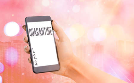 Handwriting text Quarantine. Conceptual photo restraint upon the activities of an individual or the transport of goods Modern gadgets with white display screen under colorful bokeh background 写真素材