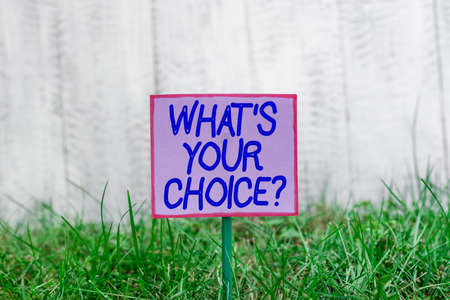 Text sign showing Whats Your Choice Question. Business photo text Option Decision Preferred Opinion Preference Plain empty paper attached to a stick and placed in the green grassy land