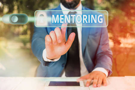 Writing note showing Mentoring. Business concept for an act or method of supporting and giving advice to a younger Graphics padlock for web data information security application system Standard-Bild