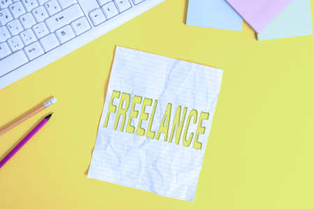 Word writing text Freelance. Business photo showcasing working at different firms rather than being permanently Copy space on notebook above yellow background with pc keyboard on the table Reklamní fotografie