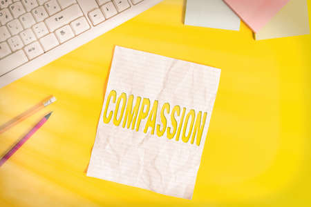 Word writing text Compassion. Business photo showcasing empathy and concern for the pain or misfortune of others Copy space on notebook above yellow background with pc keyboard on the table Banque d'images