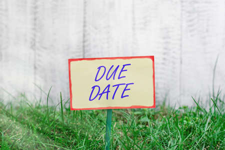 Writing note showing Due Date. Business concept for the day or date by which something is supposed to be done or paid Plain paper attached to stick and placed in the grassy land