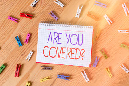 Conceptual hand writing showing Are You Covered Question. Concept meaning asking if they had insurance in work or life Colored crumpled papers wooden floor background clothespin