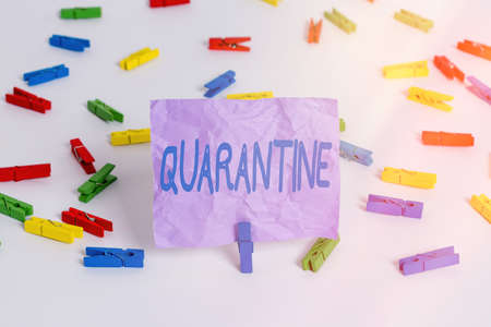 Writing note showing Quarantine. Business concept for restraint upon the activities of an individual or the transport of goods Colored clothespin papers empty reminder white floor background office