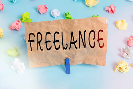 Text sign showing Freelance. Business photo text working at different firms rather than being permanently Colored crumpled papers empty reminder blue floor background clothespin