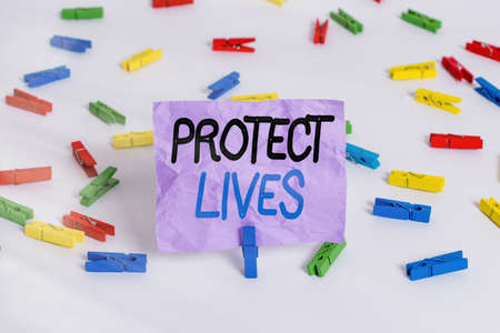 Writing note showing Protect Lives. Business concept for to cover or shield from exposure injury damage or destruction Colored clothespin papers empty reminder white floor background office