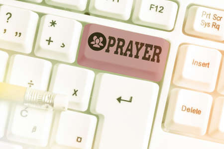 Conceptual hand writing showing Prayer. Concept meaning solemn request for help or expression of thanks addressed to God White pc keyboard with note paper above white key copy space