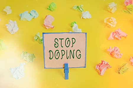 Word writing text Stop Doping. Business photo showcasing quit the use of banned athletic performanceenhancing drugs Colored crumpled papers empty reminder white floor background clothespin