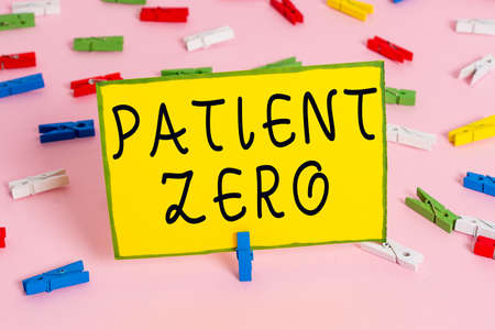 Word writing text Patient Zero. Business photo showcasing primary disease carrier of the highlycontagious disease Colored clothespin papers empty reminder pink floor background office pin