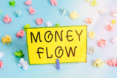 Word writing text Money Flow. Business photo showcasing it is an indicator of positive or negative in a current day Colored crumpled papers empty reminder blue floor background clothespin