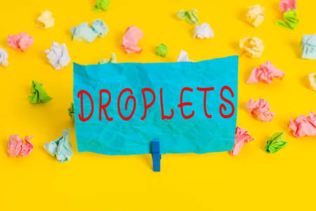 Conceptual hand writing showing Droplets. Concept meaning very small drop of a liquid can be found in certain wet places Colored crumpled paper empty reminder white floor clothespin
