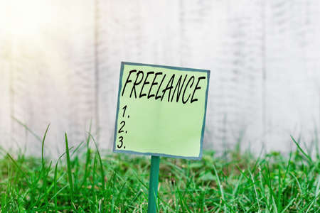 Conceptual hand writing showing Freelance. Concept meaning working at different firms rather than being permanently Plain paper attached to stick and placed in the grassy land