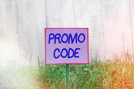 Text sign showing Promo Code. Business photo text letters or numbers that allows getting a discount on something Plain empty paper attached to a stick and placed in the green grassy land