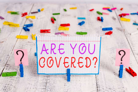Conceptual hand writing showing Are You Covered Question. Concept meaning asking if they had insurance in work or life Crumbling sheet with paper clips placed on the wooden table